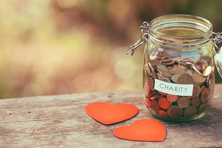 Money jar full of coins for charity and a couple of heart shapes